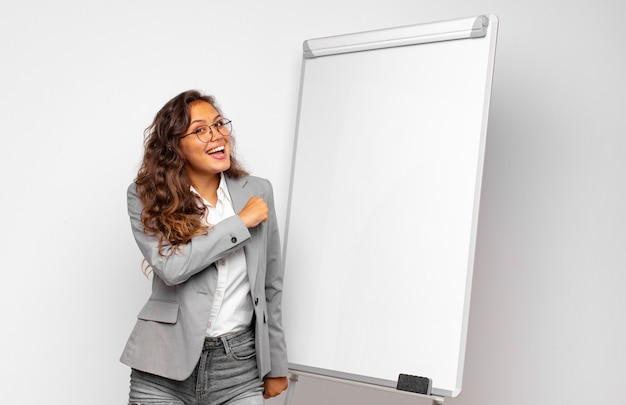 Young businesswoman feeling happy, positive and successful, motivated when facing a challenge or celebrating good results