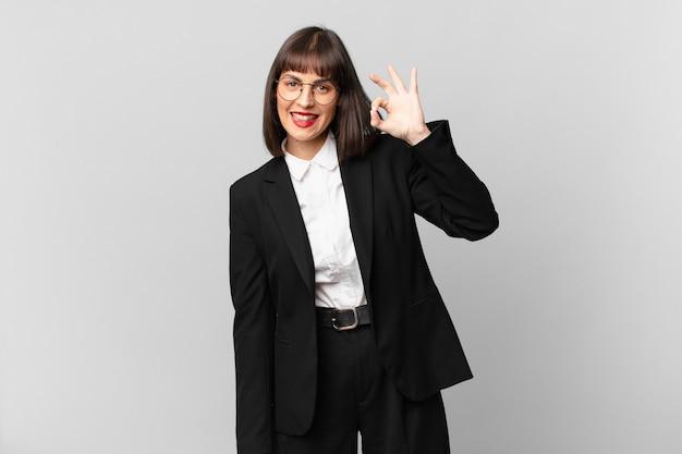 Молодая деловая женщина чувствует себя счастливой, расслабленной и удовлетворенной, демонстрирует одобрение с нормальным жестом и улыбается