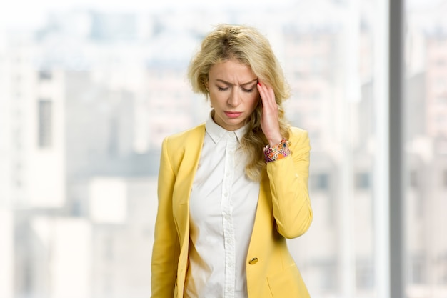 Young businesswoman feeling headache. beautiful blond lady touching her head with closed eyes and having strong headache.
