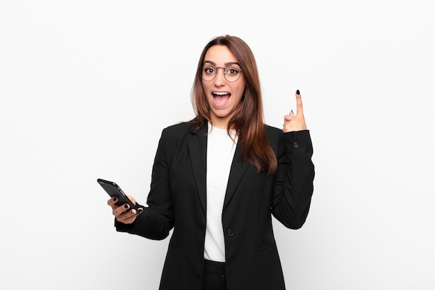 Young businesswoman feeling like a happy and excited genius after realizing an idea, cheerfully raising finger, eureka! and holding a mobile telephone
