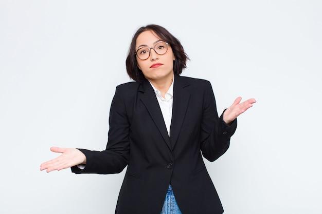 Молодая деловая женщина чувствует себя озадаченной и растерянной, неуверенной в правильности ответа или решения, пытаясь сделать выбор на фоне белой стены