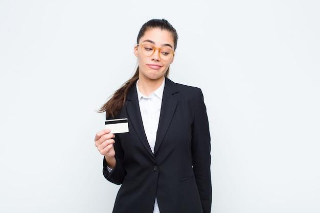Молодой предприниматель, чувствуя грусть, расстроен или рассержен и глядя в сторону с негативным отношением, нахмурившись в несогласии с банкнотами с векселями