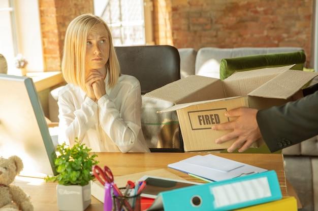 Giovane imprenditrice licenziata, sembra sconvolta. deve mettere in valigia le sue cose da ufficio e lasciare il posto di lavoro per un nuovo lavoratore. problemi di occupazione, stress, disoccupazione, nuovo stile di vita o fine carriera.
