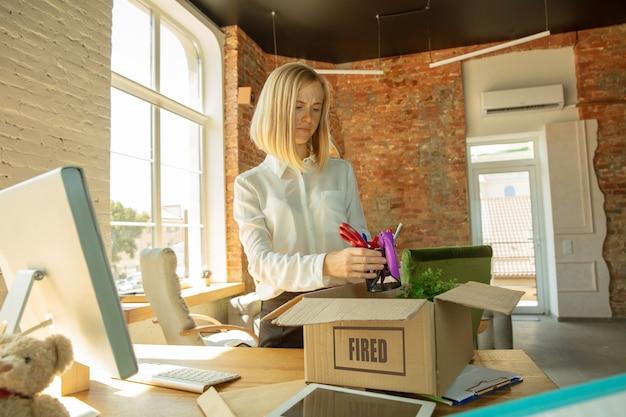 若い実業家は解雇され、動揺しているように見えます。彼女のオフィスの持ち物を梱包し、新しい労働者のために職場を離れなければなりません。職業、ストレス、失業、新しい生き方、またはキャリアの終わりの問題。
