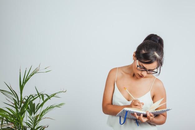 젊은 사업가 집중하고 그녀의 노트북에 쓰기