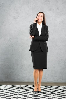 Young businesswoman in formalwear talking on cellphone standing against concrete wall