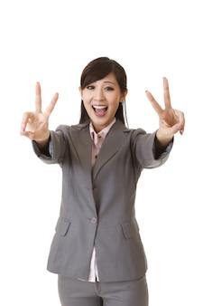 若い実業家はあなたに二重の勝利のジェスチャーと笑顔を与えます。