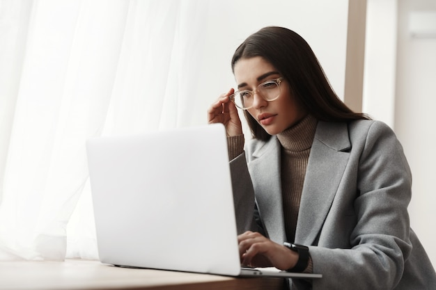 Young businesswoman in glasses sitting in an office building, working on a laptop.