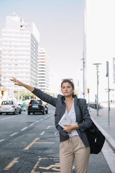 Young businesswoman hailing taxi on city street