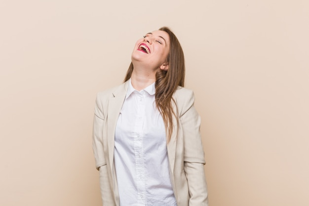 Young businesswoman happy laughing, neck stretched showing teeth.