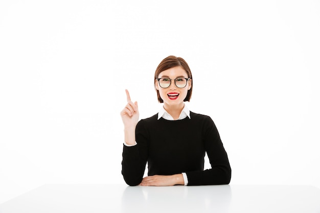 Young businesswoman having an idea, pointing up with finger