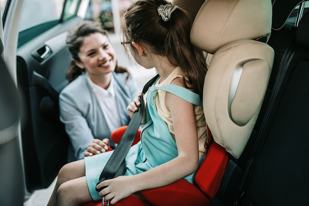 Young businesswoman helping her daughter to fasten seatbelts in the car while girl is sitting on a safety child car seat.