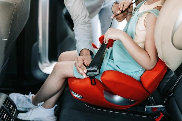 어린 여성 사업가가 안전 어린이용 카시트에 앉아 있는 동안 딸이 차 안에서 안전벨트를 매도록 도와줍니다.