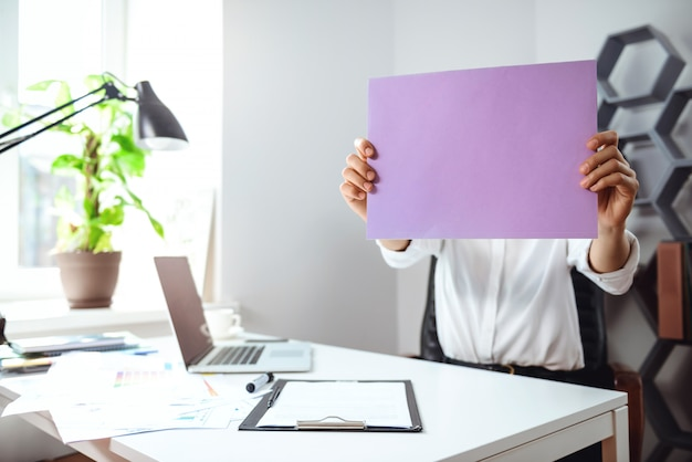 Testa nascondentesi della giovane donna di affari dietro carta nel luogo di lavoro in ufficio.