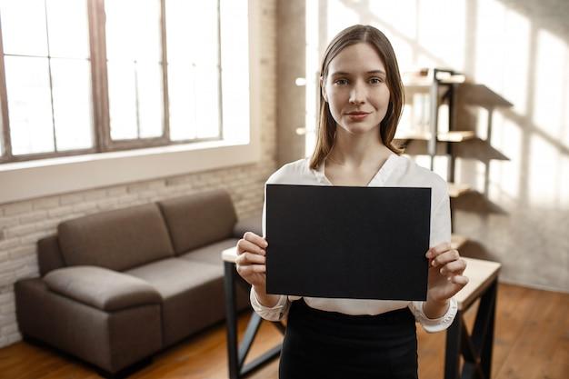 若い実業家は手で黒い机を保持します。彼女はカメラの笑顔を見てポーズをとる。明け。空の部屋。一人で。