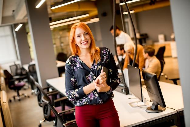 Молодая коммерсантка держа цифровую таблетку пока на заднем плане команда работая в современном офисе Premium Фотографии