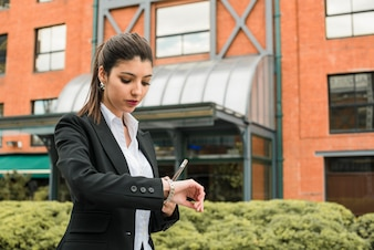 Young businesswoman holding cell phone in hand checking the time on wrist watch