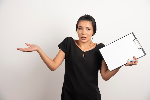 Young businesswoman holding clipboard on white wall.