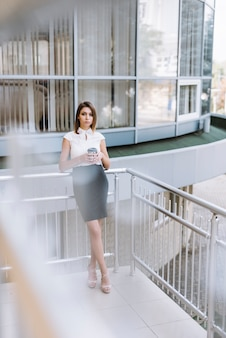 Young businesswoman holding coffee cup standing in the balcony