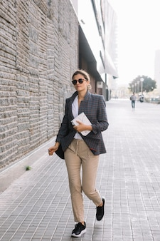Young businesswoman holding diary in hand walking on street