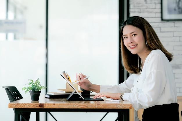 Молодая коммерсантка держа цифровую ручку работая с таблеткой, усмехаясь и смотря камеру.