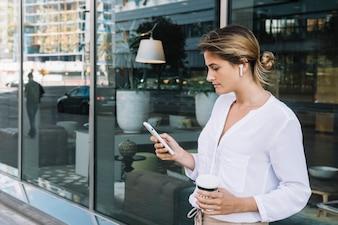 携帯電話を使用して使い捨てのコーヒーカップを保持している若い実業家