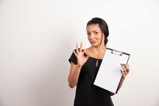 Young businesswoman holding documents and making ok sign.