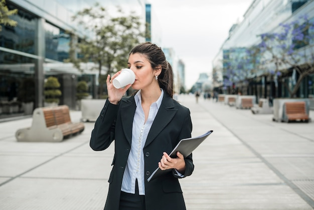 Young businesswoman holding folder in hand drinking coffee at business campus