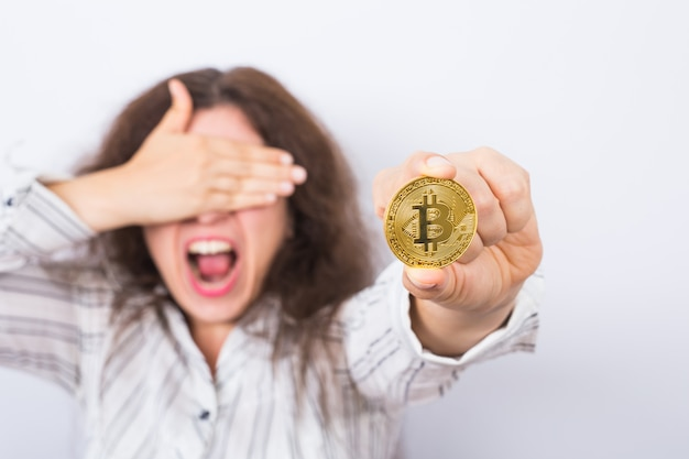 Young businesswoman holding a golden bitcoin