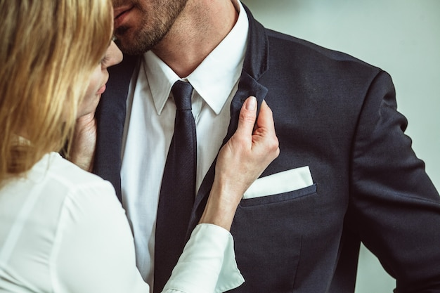 Молодая коммерсантка держа воротник куртки бизнесмена. флиртует пара неузнаваемых кавказских людей. страстный роман в офисе на рабочем месте. заделывают выстрел