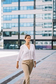 Young businesswoman holding laptop in hand walking at office campus