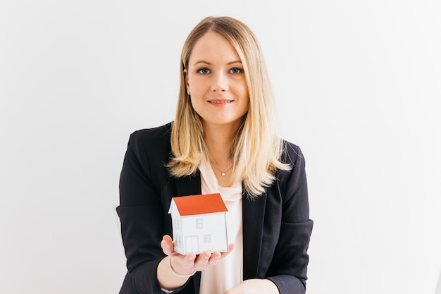 Young businesswoman holding miniature house model over white background