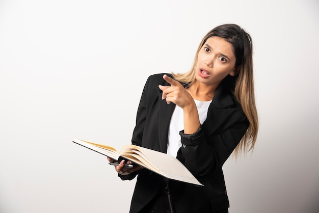 Young businesswoman holding an opened clipboard with pencil .
