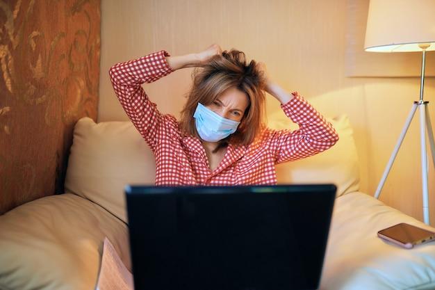 Молодой предприниматель в медицинской защитной маске работает дома за компьютером во время самоизоляции и карантина
