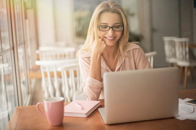 Молодой предприниматель в очках в кафе сидит, просматривая интернет на ноутбуке, радостном