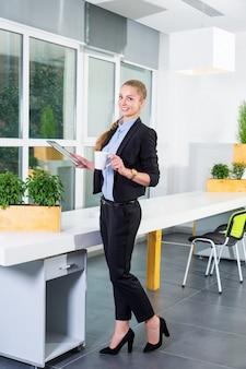 작업 목록과 태블릿을 들고 그녀의 모닝 커피를 마시는 현대 밝은 사무실에서 젊은 사업가