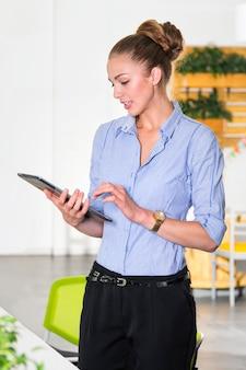 작업 목록이 태블릿을 들고 현대 밝은 사무실에서 젊은 사업가. 사무의 사업 개념입니다.