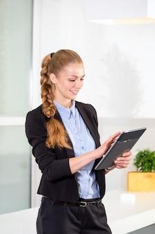 작업 목록과 함께 태블릿을 들고 현대 밝은 사무실에서 젊은 사업가