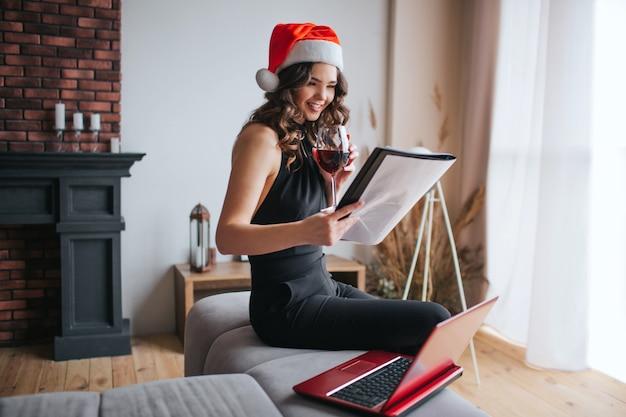 집에서 일하는 빨간 크리스마스 모자에 젊은 사업가