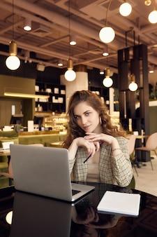 スマートカジュアルな服装の若い実業家は、コーヒーショップのインテリアでノートにメモを作る