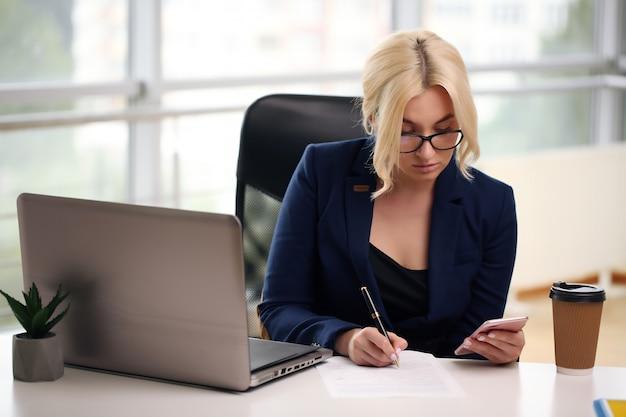 사무실에서 젊은 사업가. 그녀의 노트북에서 일하는 아름 다운 실업