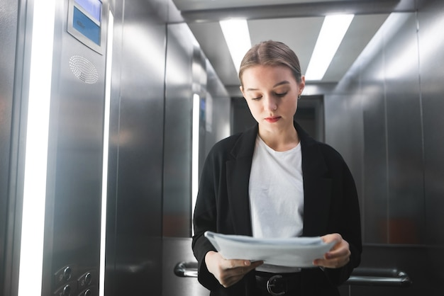 Молодой предприниматель сосредоточенно читает документы в лифте.