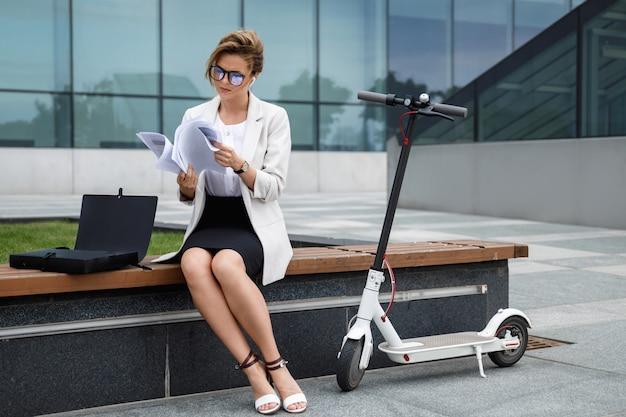 젊은 사업가 그녀의 옆에 많은 종이 문서와 전기 스쿠터와 함께 벤치에 앉아있다