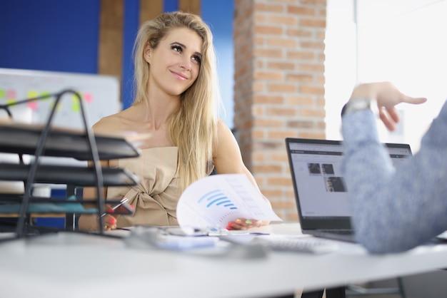 Молодой предприниматель, листая документы и общаясь с клиентом