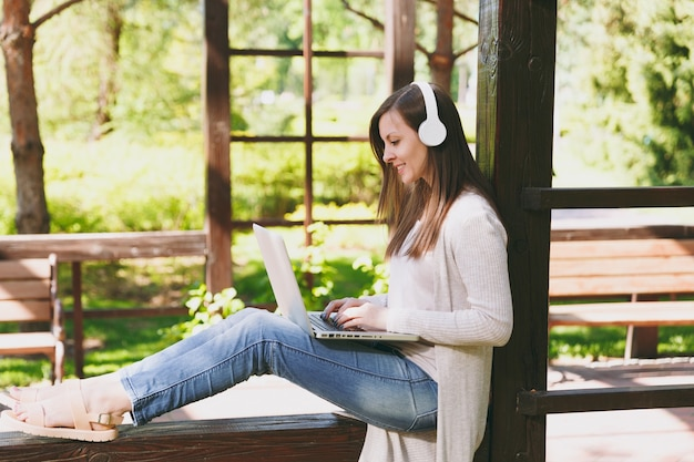 Young businesswoman in light casual clothes. woman working on modern laptop pc computer, listen music in headphones on head in street outdoors. mobile office. freelance business concept. side view.