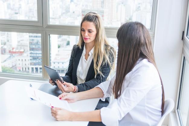 オフィスで彼女の女性の同僚と座ってデジタルタブレットを見ている若い実業家