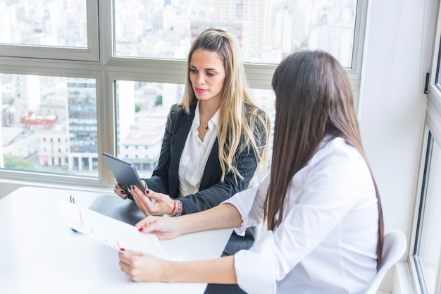 Giovane donna di affari che esamina compressa digitale che si siede con il suo collega femminile nell'ufficio