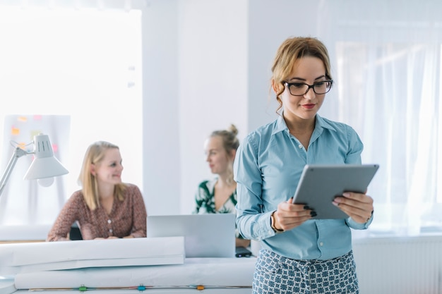 Young businesswoman looking at digital tablet standing in front of her colleagues at office