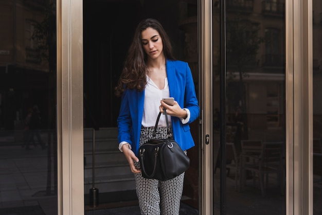 Young businesswoman looking at her handbag