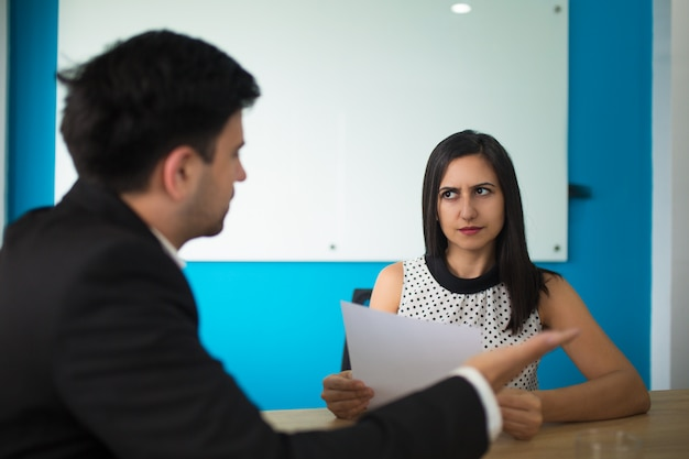 Young businesswoman looking at male partner with distrust